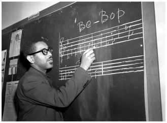 "Trumpeter Dizzy Gillespie writes a phrase of ""Be-Bop"" music on the blackboard in New York, May 1, 1947. (AP Photo)"