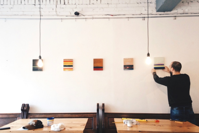 Tom Harman installs abstract paintings at Little Man Coffee Co., Cardiff. Photograph: Rhys Tranter.